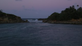 AX104_123 - 5k stock footage aerial video Flying over ocean and through a gap in the coast, Dorado, Puerto Rico, twilight
