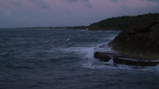 AX104_125 - 5k stock footage aerial video of the Ocean along rugged Caribbean coast, Dorado, Puerto Rico, twilight