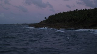 AX104_126 - 5k stock footage aerial video Flying over the ocean along rugged Caribbean shore, Dorado, Puerto Rico, twilight