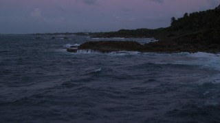 AX104_127 - 5k stock footage aerial video of the Ocean and rugged Caribbean shore, Dorado, Puerto Rico, twilight
