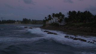 AX104_130 - 5k stock footage aerial video of Ocean along tree lined coast and oceanfront homes, Dorado, Puerto Rico, twilight