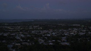 AX104_136 - 5k stock footage aerial video of Caribbean neighborhoods along the coast, Dorado, Puerto Rico, sunset