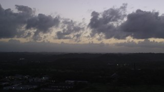 AX104_137 - 5k stock footage aerial video of Clouds over a Caribbean town, Dorado, Puerto Rico, twilight
