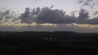 AX104_138 - 5k stock footage aerial video of Clouds over Caribbean town, Dorado, Puerto Rico, twilight