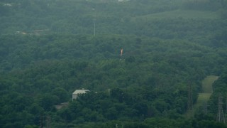 AX105_021 - 5K stock footage aerial video of a flame spout and green trees, West Mifflin, Pennsylvania
