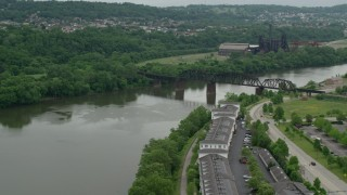 AX105_030 - 5K stock footage aerial video of Railroad Bridge near Factory, Carrie Furnace, Pittsburgh, Pennsylvania