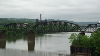 AX105_032 - 5K stock footage aerial video of Railroad Bridge near Factory, Carrie Furnace, Pittsburgh, Pennsylvania