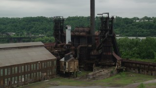 AX105_042 - 5K stock footage aerial video orbiting a steel factory, Carrie Furnace, Pittsburgh, Pennsylvania