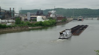 AX105_053 - 5K stock footage aerial video of River Barge near U.S. Steel Mon Valley Works, Braddock, Pennsylvania