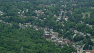 AX105_092 - 5K stock footage aerial video of homes and shops on a small town road, Penn Hills, Pennsylvania