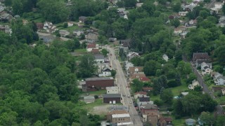 AX105_093 - 5K stock footage aerial video of shops and homes on small town road, Penn Hills, Pennsylvania