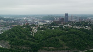 AX105_118 - 5K stock footage aerial video of downtown skyscrapers and Green Hill, Pittsburgh, Pennsylvania