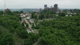 AX105_120 - 5K stock footage aerial video of hillside homes revealing downtown skyscrapers, Downtown Pittsburgh, Pennsylvania
