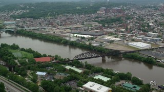 AX105_143 - 5K stock footage aerial video of a railroad bridge and riverfront warehouses, Pittsburgh, Pennsylvania