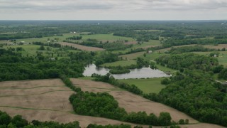 AX106_061 - 5K stock footage aerial video flying over pond and farmland in Enon Valley, Pennsylvania