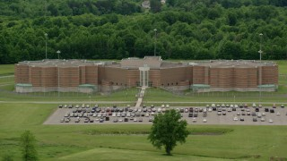 AX106_086 - 5K stock footage aerial video orbiting the parking lot outside the Ohio State Penitentiary, Youngstown, Ohio