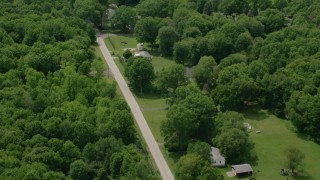 AX106_140 - 5K stock footage aerial video flying over rural homes and country road in Windham, Ohio