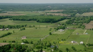 AX106_142 - 5K stock footage aerial video of farmland and country road in Windham, Ohio
