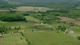 AX106_143 - 5K stock footage aerial video of farmland and red barns in Windham, Ohio