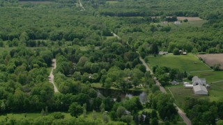 AX106_144 - 5K stock footage aerial video of a country road by farms in Garrettsville, Ohio