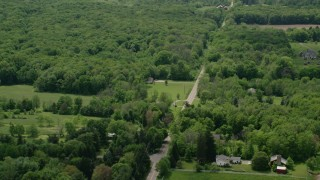 AX106_145 - 5K stock footage aerial video of a country road and forest in Garrettsville, Ohio