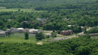 AX106_147 - 5K stock footage aerial video orbiting campus buildings and football field at Hiram College, Ohio