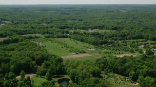 AX106_150 - 5K stock footage aerial video  flying over rural homes and forest in Hiram, Ohio