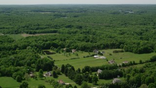 AX106_151 - 5K stock footage aerial video  flying over rural homes by forest in Hiram, Ohio