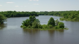 AX106_158 - 5K stock footage aerial video flying by a tiny island with trees in Akron City Reservoir, Chagrin Falls, Ohio
