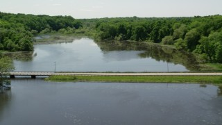 AX106_162 - 5K stock footage aerial video flying over bridge and revealing rural homes by Akron City Reservoir, Chagrin Falls, Ohio