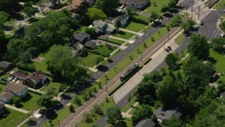 AX106_191 - 5K stock footage aerial video of a commuter train and suburban homes in Cleveland, Ohio