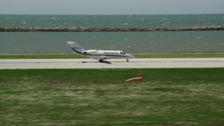 AX106_269 - 5K stock footage aerial video tracking Private Jet Taking Off from Cleveland Burke Lakefront Airport, Ohio