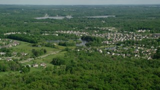 AX107_067 - 5K stock footage aerial video approaching a lakeside suburban neighborhood, Aurora, Ohio