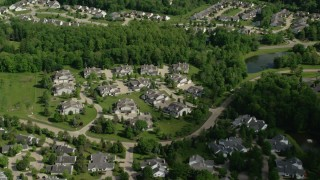 AX107_073 - 5K stock footage aerial video flying over trees and lakeside homes, Aurora, Ohio