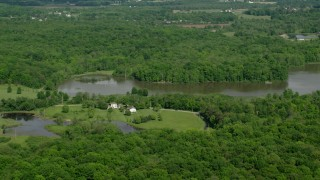AX107_076 - 5K stock footage aerial video of isolated lakeside home surrounded by trees, Aurora, Ohio