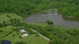 AX107_077 - 5K stock footage aerial video of isolated lakeside home surrounded by trees, Aurora, Ohio