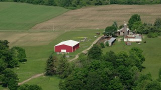 AX107_079 - 5K stock footage aerial video flying by a farm with a red barn, Aurora, Ohio