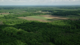 AX107_087 - 5K stock footage aerial video flying over farms and trees, Ravenna, Ohio