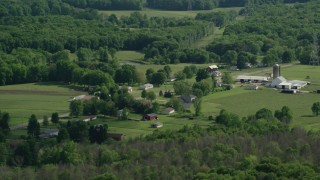 AX107_090 - 5K stock footage aerial video of barns and farmland along a country road, Ravenna, Ohio