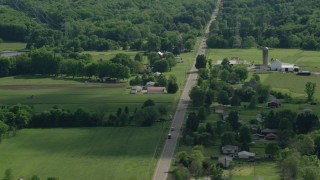 AX107_091 - 5K stock footage aerial video of barns and farmland along a country road, Ravenna, Ohio