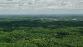 AX107_092 - 5K stock footage aerial video flying over forest toward a reservoir, Ravenna, Ohio