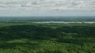 AX107_093 - 5K stock footage aerial video flying over forest toward a reservoir, Ravenna, Ohio