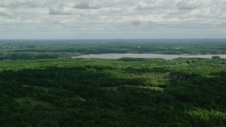AX107_094 - 5K stock footage aerial video flying over forest approaching a reservoir, Ravenna, Ohio