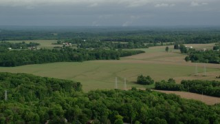 AX107_103 - 5K stock footage aerial video flying over trees and farmland, Columbiana, Ohio
