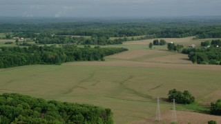 AX107_104 - 5K stock footage aerial video passing by farmland, Columbiana, Ohio