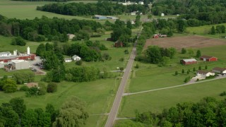 AX107_105 - 5K stock footage aerial video following a country road past barns and farmland, Columbiana, Ohio