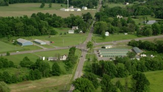 AX107_106 - 5K stock footage aerial video following a country road past barns and farmland, Columbiana, Ohio