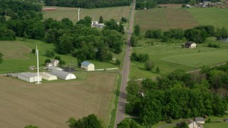 AX107_107 - 5K stock footage aerial video of barns and farms along a country road, Columbiana, Ohio