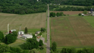 AX107_108 - 5K stock footage aerial video of country road through farmland toward forests, Columbiana, Ohio