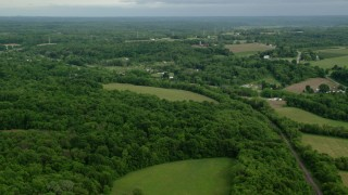 AX107_111 - 5K stock footage aerial video flying over forests toward rural homes, East Palestine, Ohio